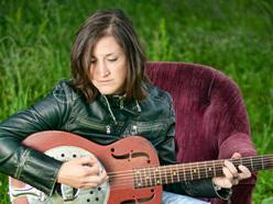 Kelcy_Mae_chair_grass_guitar_ReverbNation
