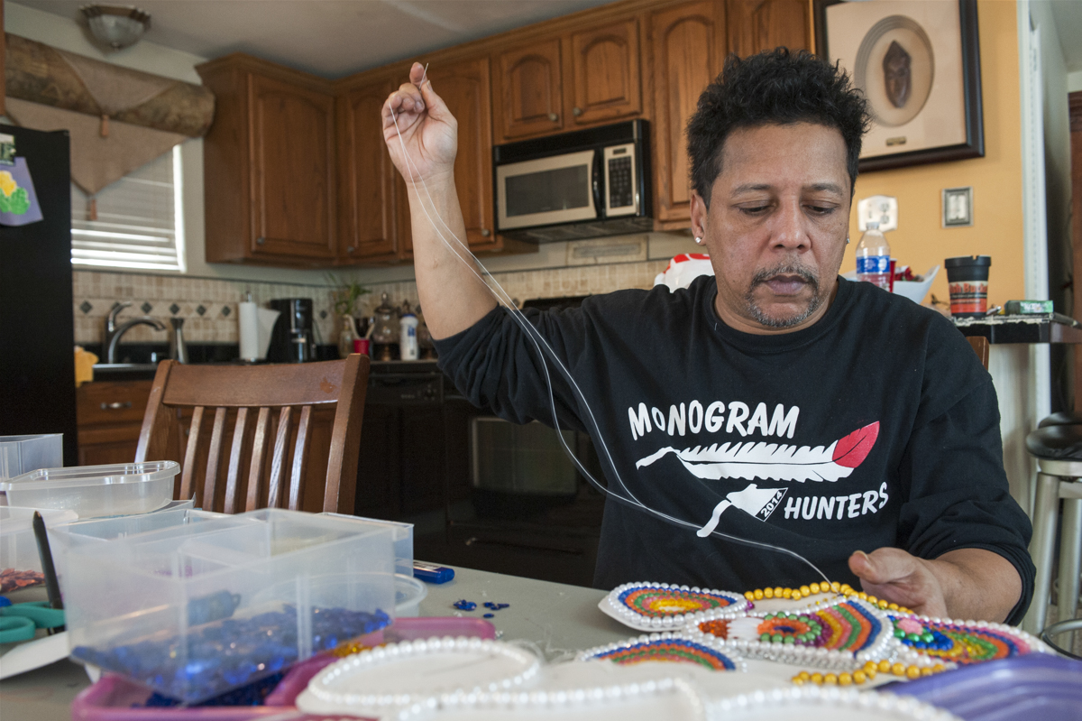 """Big Chief Tyrone """"Pie"""" Stevenson at home sewing for Mardi Gras 2015 on January 8, 2015."""