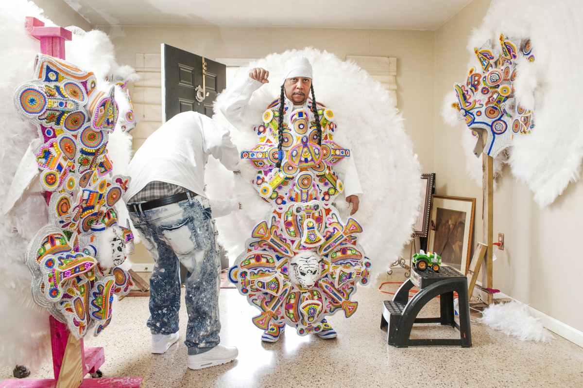 """Monogram Hunters Big Chief """"Pie"""" Tyrone Stevenson puts on his white suit for the first time with the help of his son Tyrone Jr. on Fat Tuesday 2015. Starting at age 12 Big Chief Pie suited with Yellow Pocahontas until he was given his own tribe in 92 Monogram Hunters, which was Yellow Pocahontas' Big Chief Tootie Montana's fathers tribe's name."""