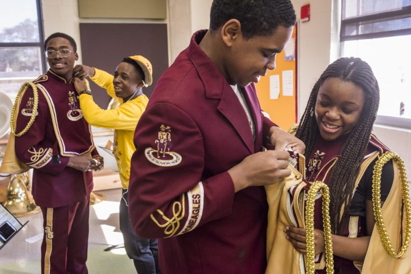 Nigel Tapp gets help from Terry Williams Jr. while Darryl Cole helps Kendra Boseman with their McDonogh 35 Senior High School uniforms in the band room before they march with in Mystic Krewe of Femme Fatale parade on February 24, 2019.