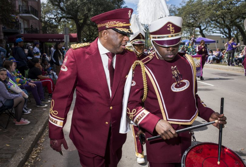 McDonogh 35 Senior High School Marching Band Director Lawrence Rawlins talks with Terry Williams while marching down St Charles for the Mystic Krewe of Femme Fatale parade on February 24, 2019.