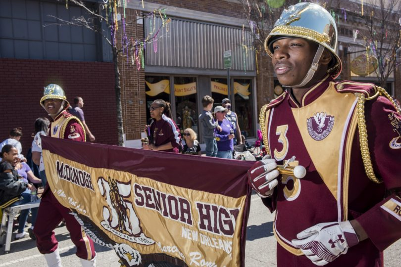 McDonogh 35 Senior High School Marching Band members Veshawn Phillips (front) and Claudell McDonald hold their school banner in the CBD during the Mystic Krewe of Femme Fatale parade on February 24, 2019.