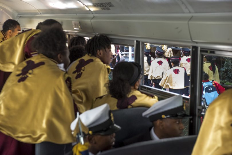 McDonogh 35 Senior High School Marching Band members watch Helen Cox High School Marching Band pass their bus after the Mystic Krewe of Femme Fatale parade on February 24, 2019.